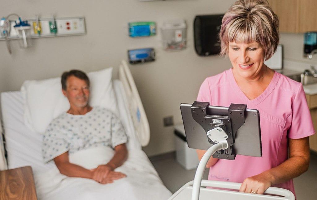 Smiling healthcare worker on a tablet using a Moffatt flexarm