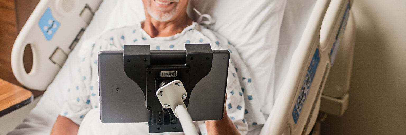 Man in hospital bed using a device on a flex arm