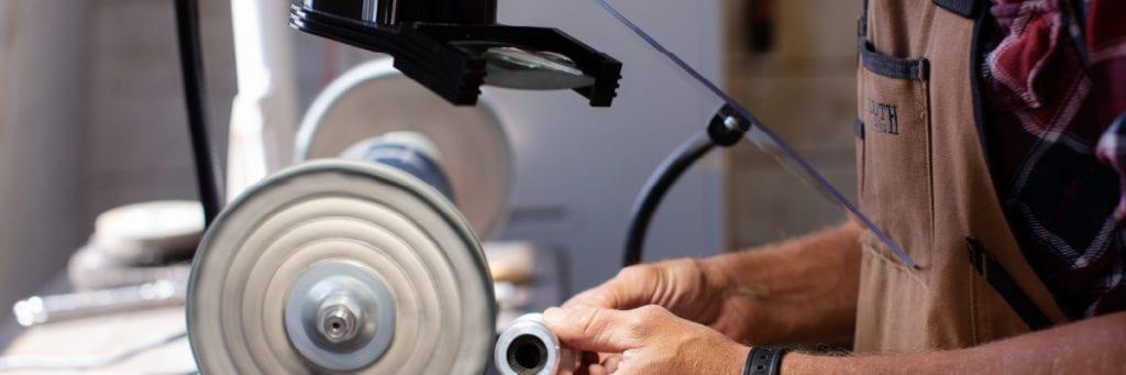 Man polishing metal while using a flex arm protective shield
